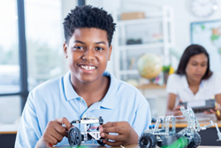 Independent African American male STEM student builds a robotic vehicle during robotics class. He is concentrating while he works on the project.